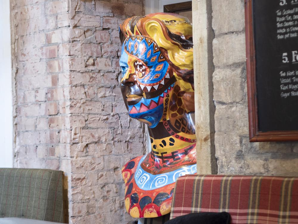 The Queen's Head Peterborough - a colourful sculpture of the queens head painted in bright colours