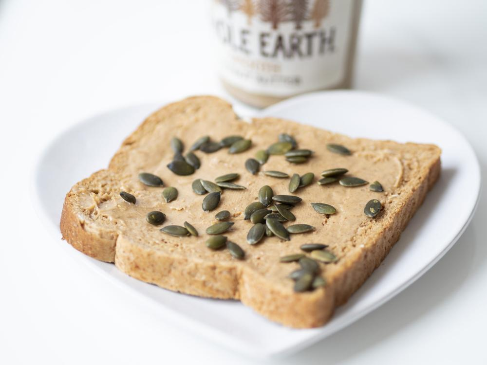 Protein packed vegan breakfast consisting of wholegrain oat seeded bread spread with peanut butter and sprinkled with pumpkin seeds