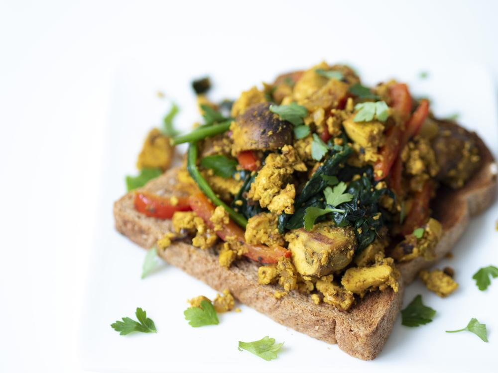 Protein packed vegan breakfast of scrambled tofu with slices of red pepper, spinach and mushroom piled on top of a toasted slice of wholegrain bread