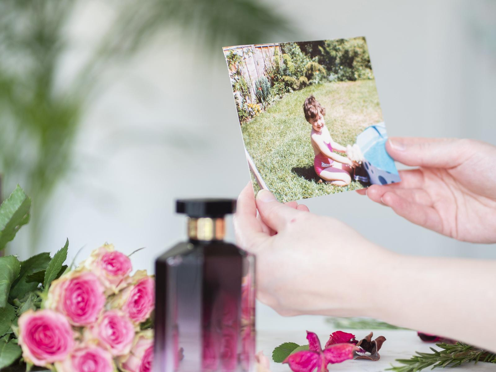 Mother's Day Love Notes with Boots Perfume - Laura holding a picture of herself as a toddler kneeling on green grass in a flowering garden next to a paddling pool