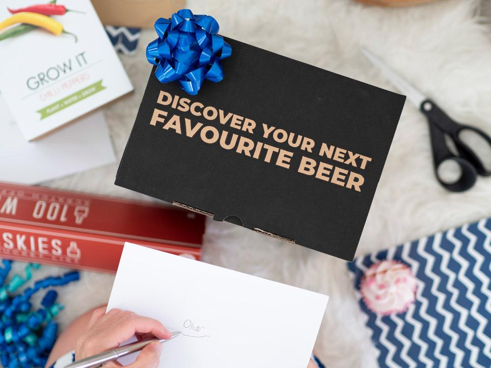 """Discover your next favourite beer"" Beer Hawk gift box surrounded by wrapping paper and other presents 