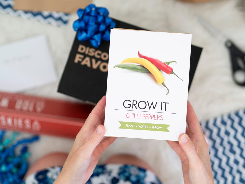 "Looking down on hands holding a ""Grow It Chilli Peppers"" gift box 