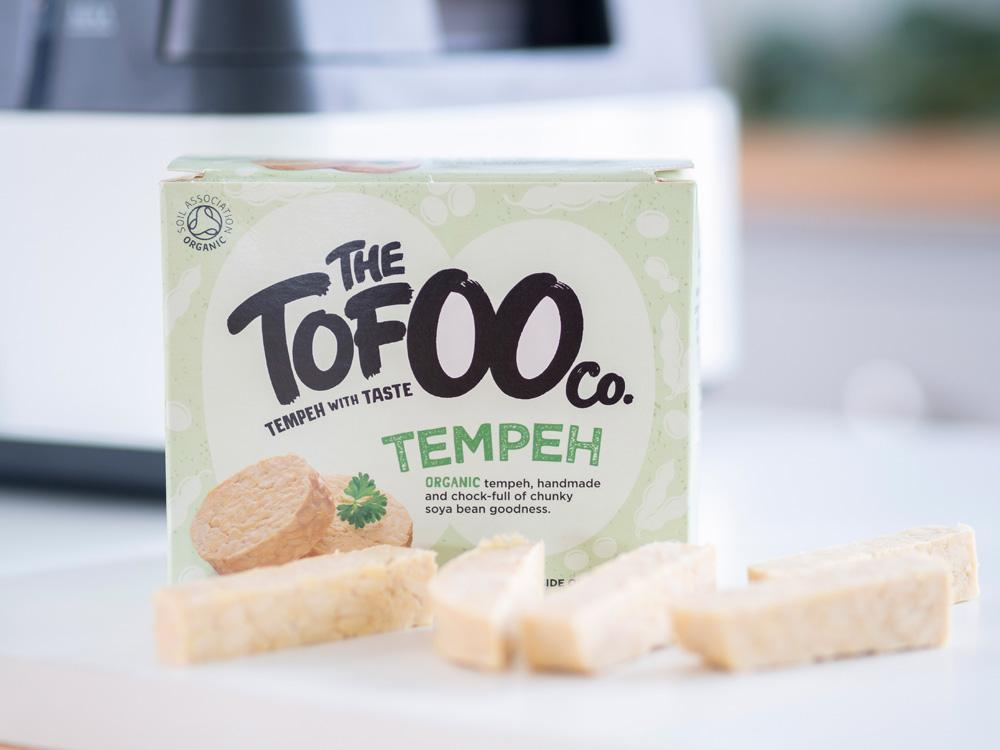 A packet of The Tofoo Co. Tempeh with chopped batons of tempeh in the foreground.