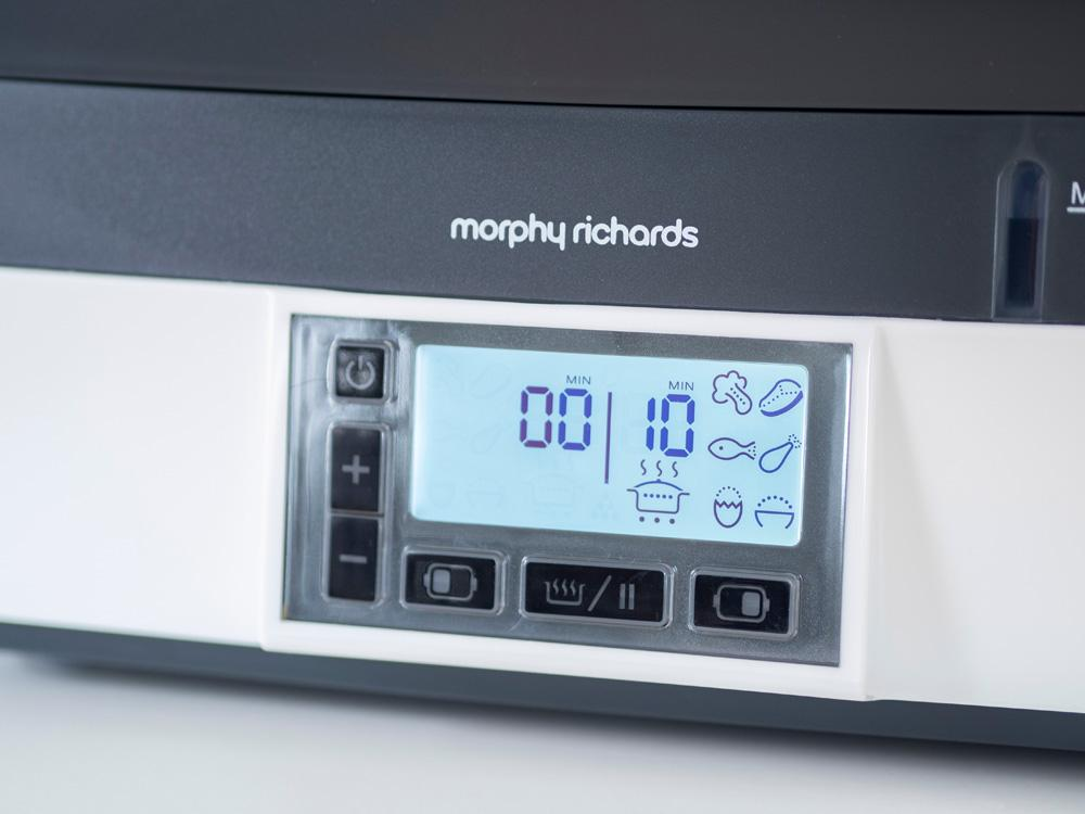 Close up of the control panel on the Morphy Richards Intellisteam Compact electric food steamer, sitting on a tabletop in front of a kitchen cabinet.