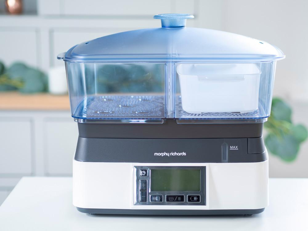 Front view of the Morphy Richards Intellisteam Compact electric food steamer, sitting on a tabletop in front of a kitchen cabinet.