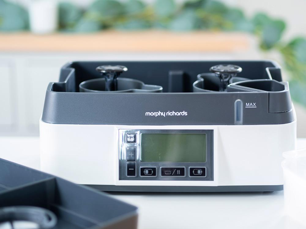 The base of the Morphy Richards Intellisteam Compact electric food steamer, sitting on a tabletop in front of a kitchen cabinet.