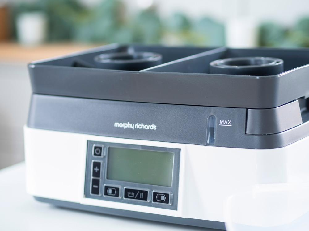 A view of the drip tray which sits on the base of the Morphy Richards Intellisteam Compact electric food steamer, sitting on a tabletop in front of a kitchen cabinet.