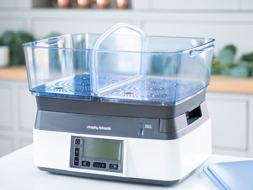 The Morphy Richards Intellisteam Compact electric food steamer, with the main compartment attached, sitting on a tabletop in front of a kitchen cabinet.
