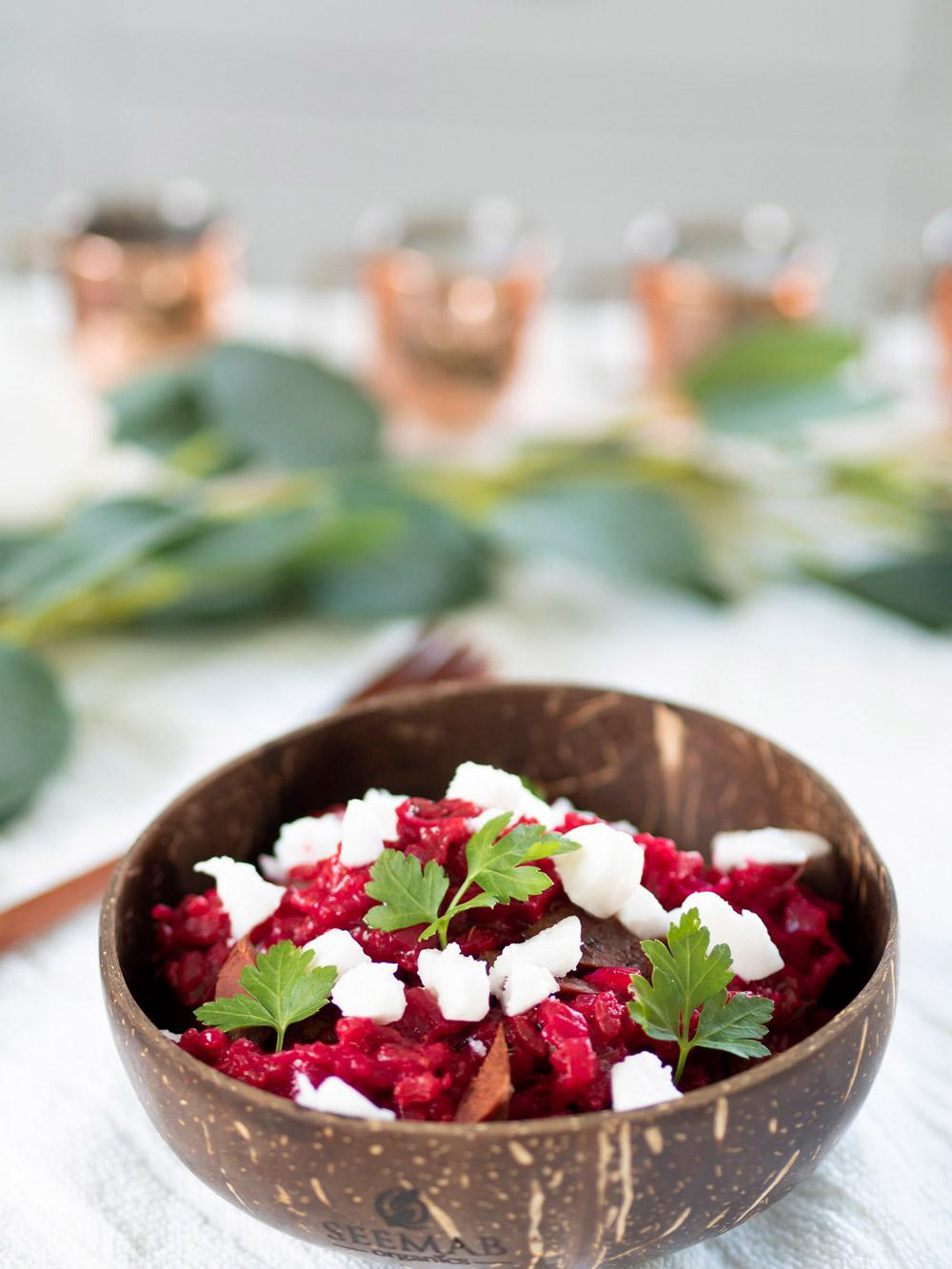 Simple but delicious quick beetroot risotto (vegan) | A coconut bowl filled with vegan risotto which is topped with chunks of vegan feta cheese and garnished with sprigs of parsley leaves. Blurred in the background is a decorative branch of eucalyptus leaves and a row of copper mugs.