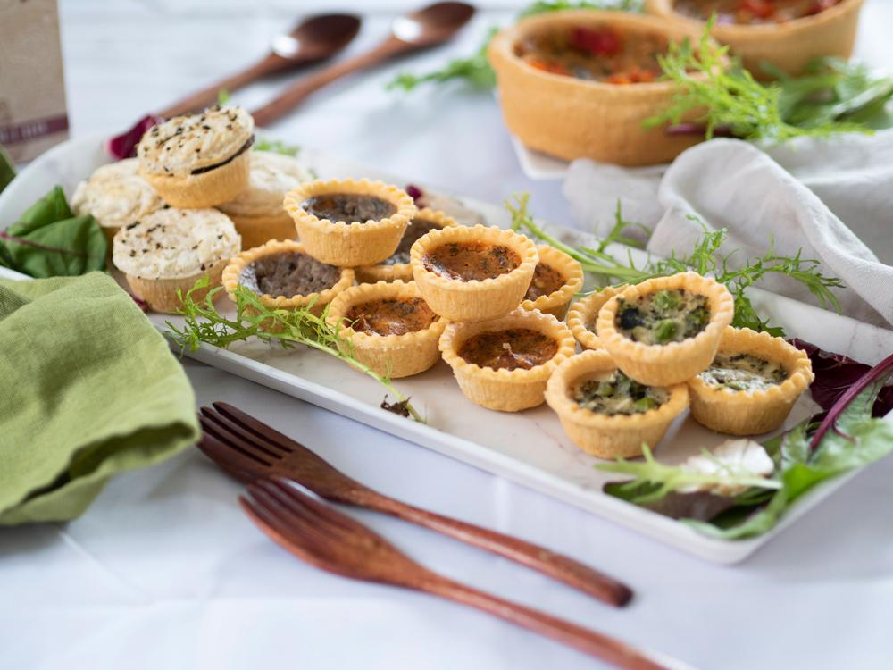 Vegan Festive Favourite Foodie Finds - A large selection of mini pies and quiches are assembled on a marble tray with salad garnishes. The tray is on a white tablecloth, in front of Laura's welsh dresser.