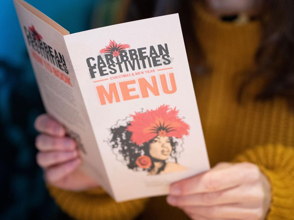 Laura is wearing a knitted jumper, holding a copy of the Carribbean Festivities Turtle Bay Festive Menu