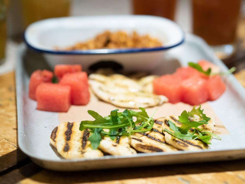 A tray of appetisers from the Turtle Bay Festive Menu. Slices of grilled flatbread with charred grill lines are arranged overlapping in a row and decorated with rocket. In the background are cubes of melon and a tray of chickpeas.