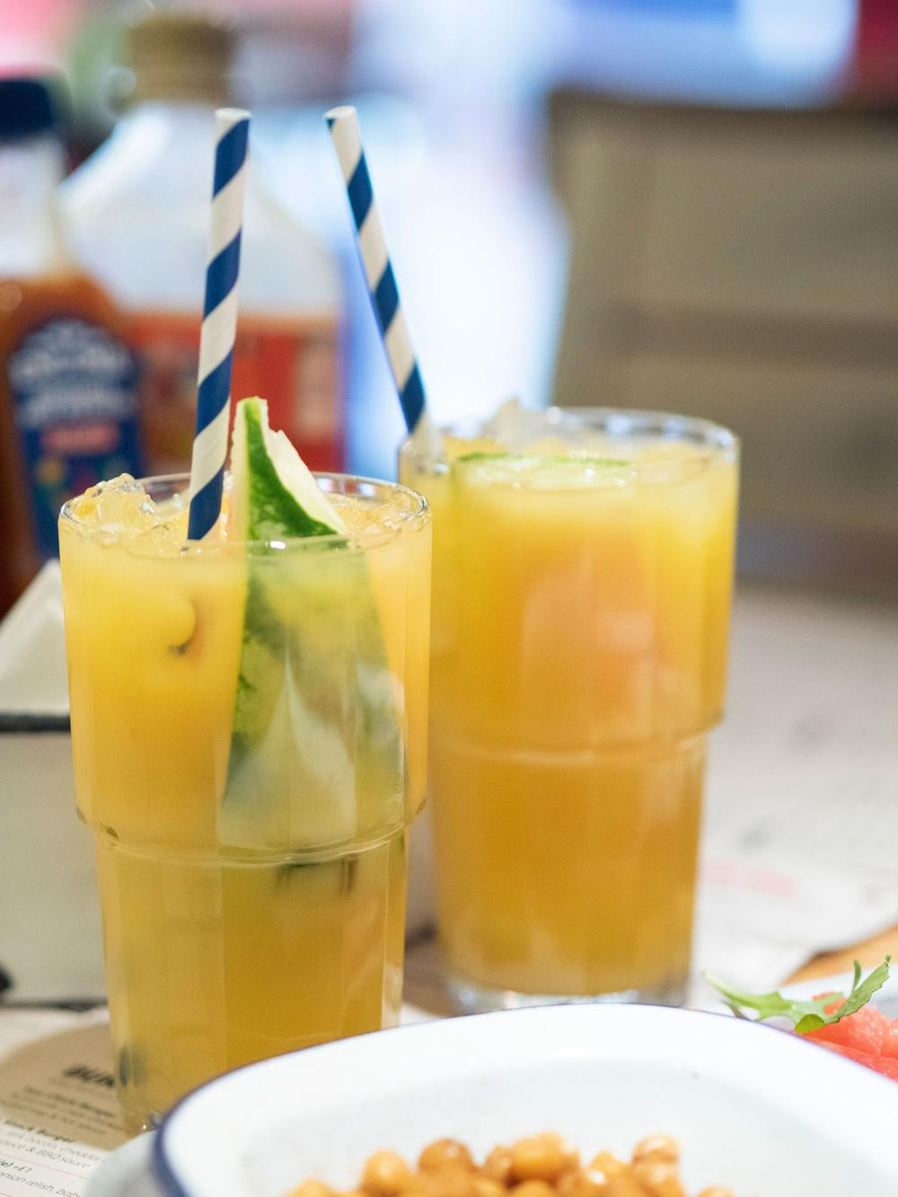 Two mango and passionfruit cocktails in tall glasses decorated with blue and white stripey straws and slices of melon.