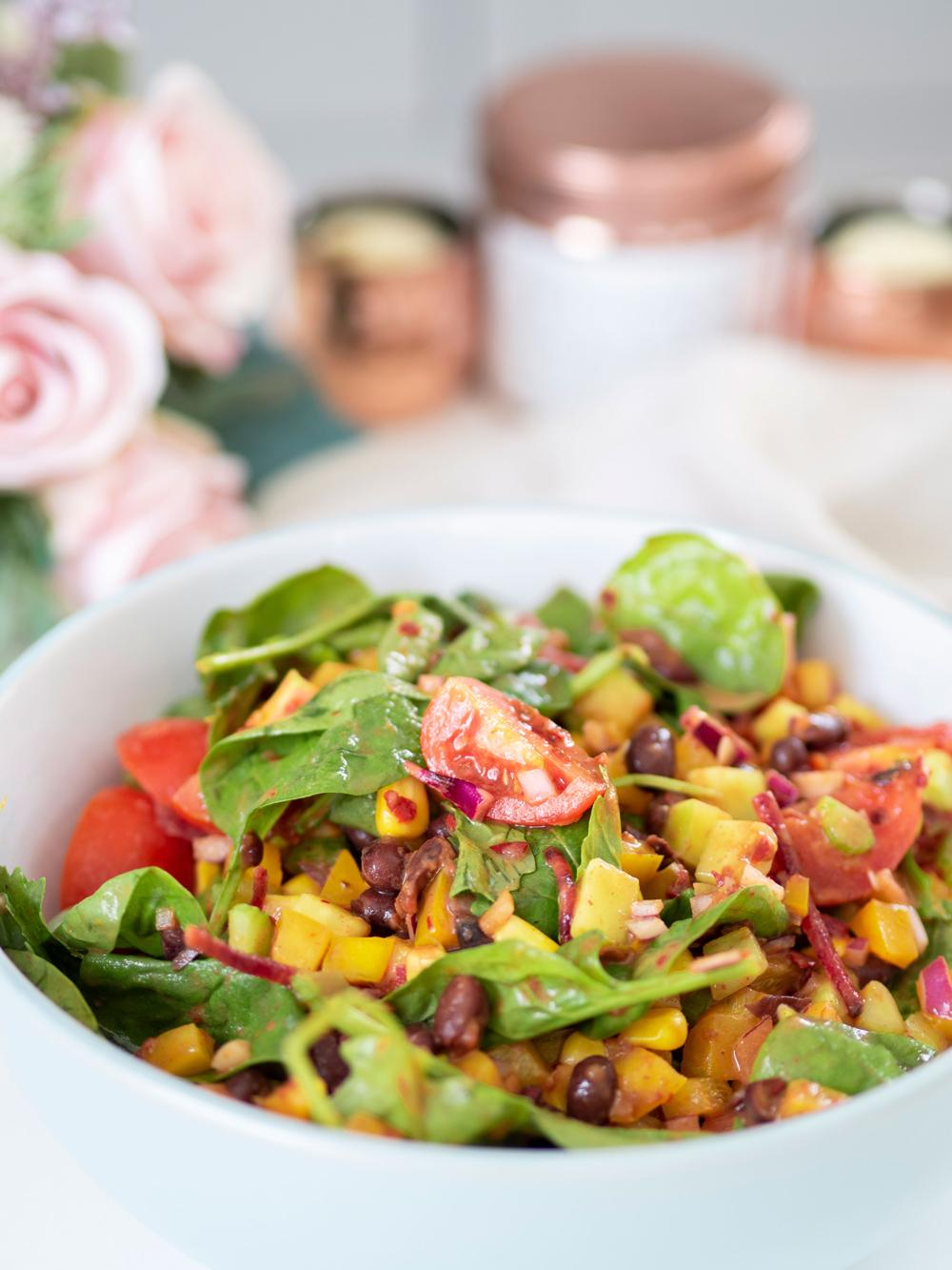 Spicy Warm Bean Salad - cover photo showing a bowl of the salad in front of a backdrop of table flowers and candles.