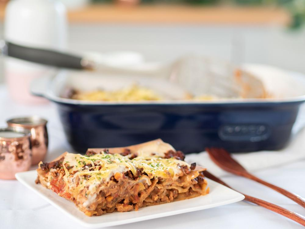 Laura's Loaded Lasagna Hidden Veg cover photo - a slice of the lasagna in front of the ceramic dish containing the rest of the baked lasagna. There's melted cheese on top and you can see the layers of bolognese sauce, vegetables and white sauce.