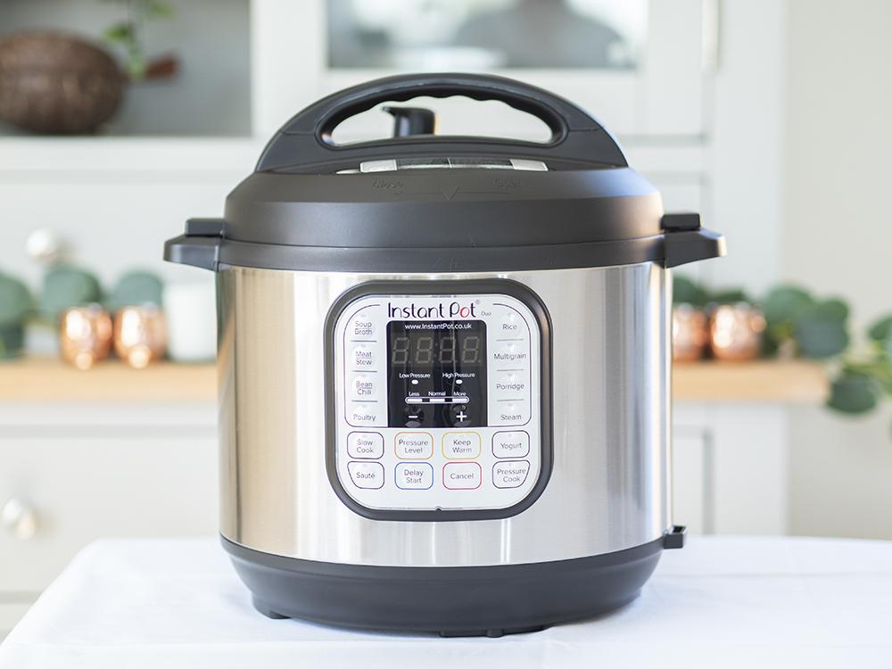Guide to using the Instant Pot Pressure Cooker - title image featuring a front facing shot of the instant pot with its lid on.